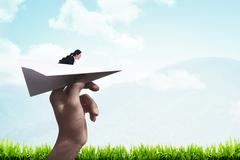 Business woman ready to launch with paper plane - stock photo
