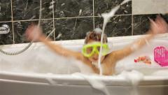 Little girl with a diving mask plays in a bathtub with foam Stock Footage