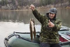 Fisherman in a boat holding a caught burbot Stock Photos