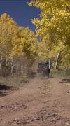 Stock Video Footage of Autumn 4x4 recreation vehicle drives away mountain trail vertical HD 009