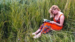 Charming blonde in a red dress reading a book sitting in the grass. Slow motion. Stock Footage