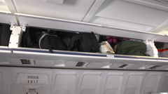 Airline passenger pushes carryon  bag into full overhead bin Stock Footage