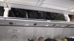 Cabin crew closing overhead bins ready for take off Stock Footage