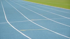 Young boy running on blue track in the stadium in day time to practice himself Stock Footage