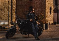 Man with a cafe-racer motorcycle outdoors - stock photo