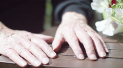 4K Close up on clasped hands of elderly man on garden table Stock Footage