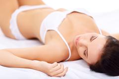 Attractive alluring girl lying on bed - stock photo