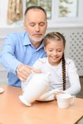 Grandfather and little girl having tea party - stock photo