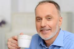 Agreeable man drinking tea Stock Photos