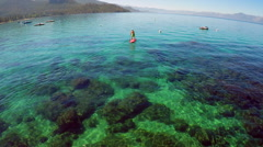 An aerial shot over a paddle boarder rowing on Lake Tahoe. Stock Footage