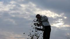 Man with broom silhouette sweeps on sky background slow motion Stock Footage