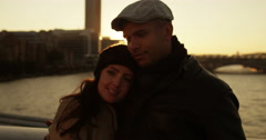 Shot of an attractive young couple in love with the sun sets in the background. Stock Footage