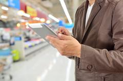 Young Man Hands holding Tablet in Supermarket - stock photo