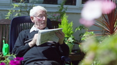 4K Elderly man in the garden doing a crossword puzzle in the newspaper Stock Footage