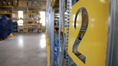 Stock Video Footage of Fork-lift truck is coming closer to the racks