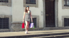 Happy woman walking on steps with shopping bags, steadycam shot - stock footage
