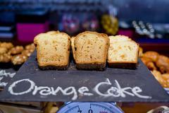 Sliced orange breads on black board and Orange cake hand-sketched typographic - stock photo