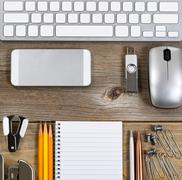 Workspace with simple office supplies on aged desktop - stock photo