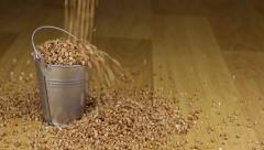 Fall into a bucket of buckwheat grains and on wooden floor Stock Footage