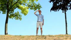 Young man comes to hillock stands between trees and observes surroundings Stock Footage