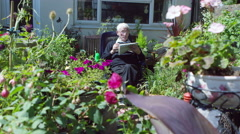 4K Elderly man in the garden doing a crossword puzzle in the newspaper - stock footage