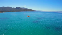 An aerial shot of a woman and man sitting on a paddle board on Lake Tahoe. Stock Footage