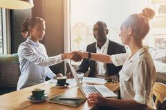 Black business woman and white business woman shaking hands - stock photo