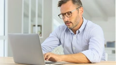 Handsome 40-year-old man at home using laptop Stock Footage