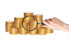 golden coins and hand holding magnifying glass isolated on white - stock photo