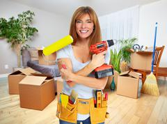 Beautiful woman with drill and paint roller. - stock photo