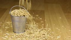 Fall into a bucket of oats grains and on wooden floor Stock Footage