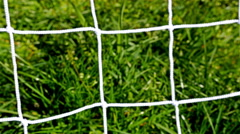 Soccer ball kicked in a football door, close up of tha ball and the net - stock footage
