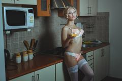 Girl in the kitchen lingerie and stockings. - stock photo