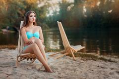 Girl is sitting deck chair beach near the lake. - stock photo