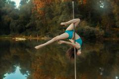 Girl revolves on the pole for dancing performing tricks. - stock photo