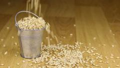 Fall into a bucket of pearl barley grains and on wooden floor Stock Footage