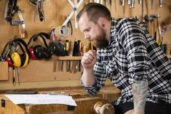 Carpenter planning work and looking at drawings in the workshop Stock Photos