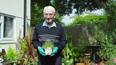 4K Portrait of elderly man in the garden holding a pot of flowers.  - stock footage