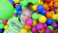 Cute kid laying among many colorful plastic toy balls at children playground Stock Footage