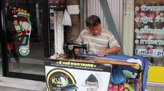 Tailor on a city street. Southeast Asia Stock Footage