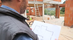 Construction manager checking blueprint on site - stock footage