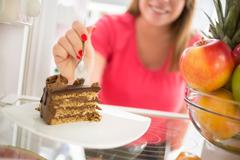 Tasty piece of chocolate cake attracts girl to eat it - stock photo