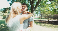 Camera flying around a beautiful young couple. Young adults are in the park Stock Footage
