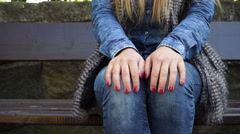 Woman stressed hands sitting on bench in autumn park 4K - stock footage