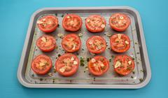 Tomatoes on a baking tray ready for roasting - stock photo