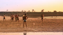 Local village youth playing football near Irrawaddy river at sunset. Myanmar - stock footage