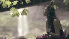 Model Sits Beneath Tree, Looks Around, Beautiful Waterfall In Background - stock footage