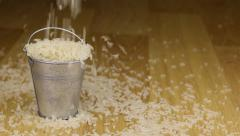 Fall into a bucket of rice grains and on wooden floor Stock Footage