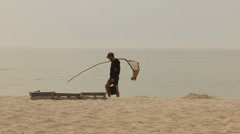 The fisherman passes along the beach Stock Footage