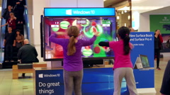 Stock Video Footage of Children dancing with Microsoft demonstrated game beside Window store
